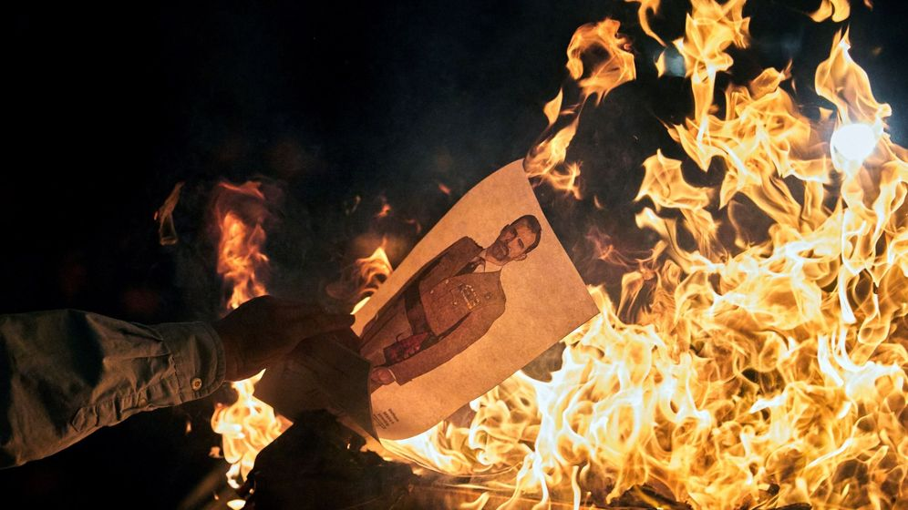 Foto: Varios manifestantes queman fotos del rey Felipe en una concentración convocada por los CDR en Girona. (EFE)