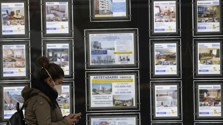 Una mujer pasa por delante de un portal inmobiliario de venta y alquiler. (EFE)