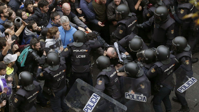 Agentes antidisturbios forman un cordón de seguridad ante el colegio Ramón Llull de Barcelona, este 1-O. (EFE)