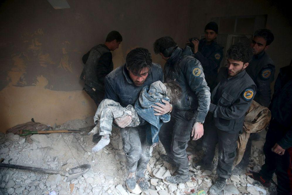 Foto: Un hombre socorre a un menor herido en una ataque aéreo ruso en Douma, al Este de Damasco, el 10 de enero de 2016 (Reuters).