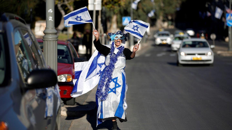 Una mujer cubierta de banderas israelíes baila por las calles de Jerusalén. EFE