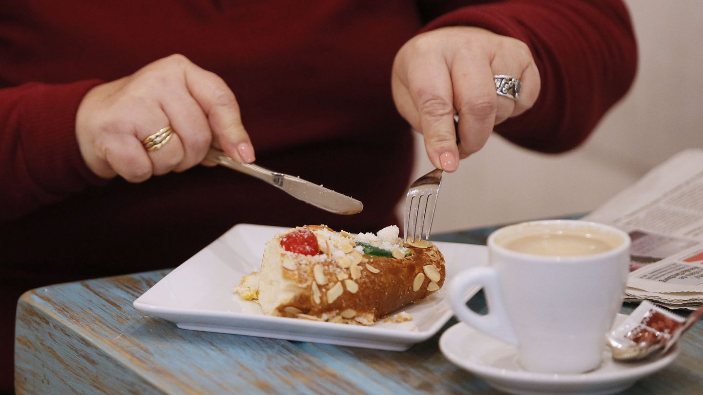 Una mujer desayuna un trozo de roscón por el Día de Reyes (EFE/Mariscal)