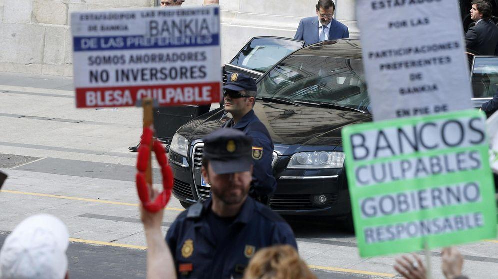 Foto: Protesta de los afectados por las preferentes con Rajoy al fondo. (EFE)