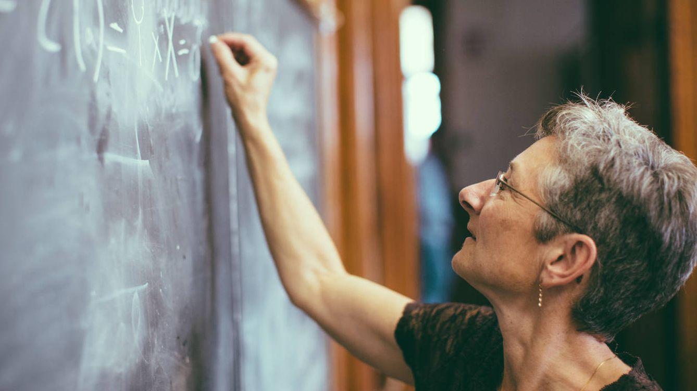 Foto: Dramatización de la profesora viral escribiendo en la pizarra un mensaje que cambiará la vida de miles de personas (obviemos que es una fómula matemática). (iStock)