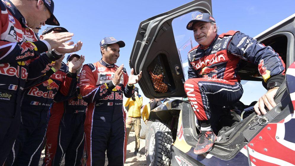 Foto: Carlos Sainz, bajando del Mini aplaudido por Al-Attiyah y algunos de sus principales rivales. (EFE)