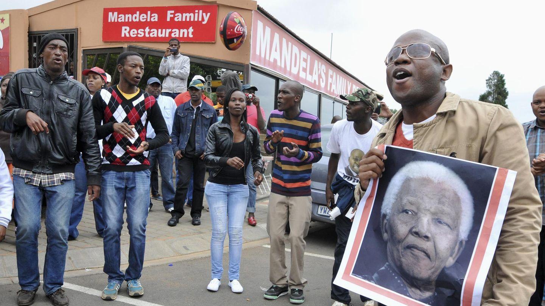 Sudafricanos bailan y cantan en la calle en homenaje a Mandela en Soweto (Reuters).