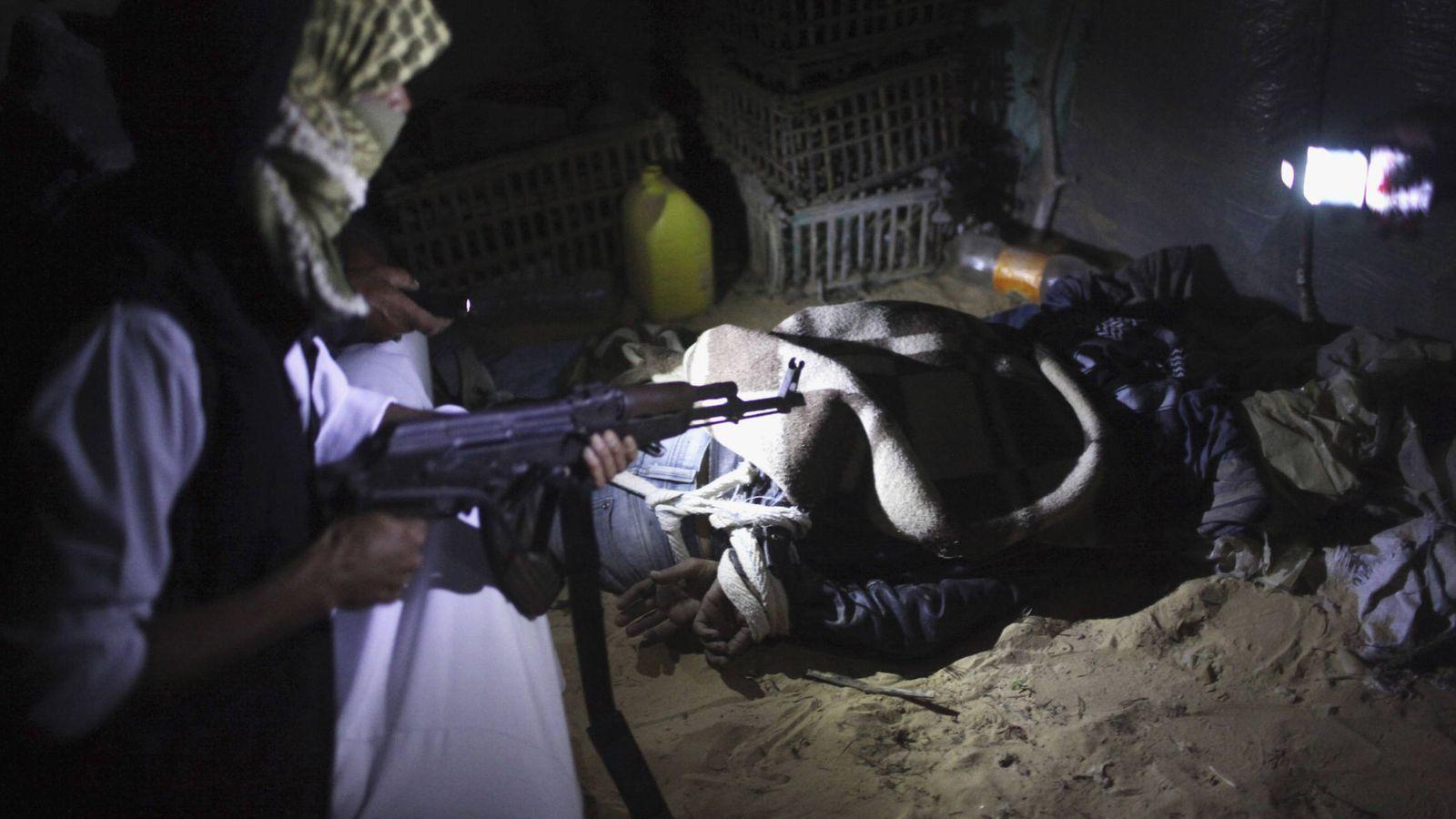 Foto: Un beduino armado custodia a un inmigrante ilegal en el norte del Sinaí, antes de introducirle de forma clandestina en Israel. (Reuters)