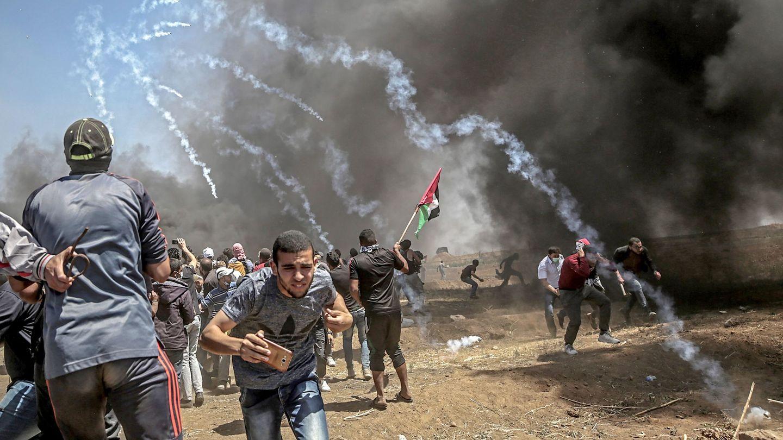 Manifestantes corren para protegerse del gas lacrimógeno lanzado por soldados israelíes durante unas protestas en la frontera de Gaza e Israel, el 14 de mayo de 2018 (EFE).