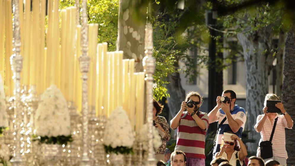 Foto: Turistas fotografían, en una imagen de archivo, un paso de procesión en Sevilla (EFE)