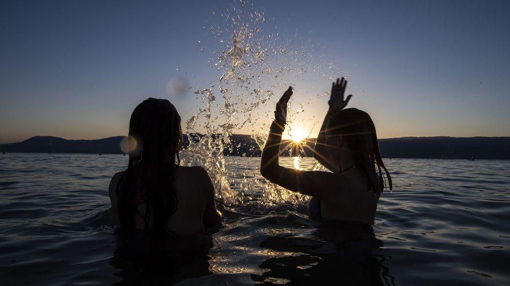 Foto: Dos adolescentes disfrutan de la puesta de sol en el agua (EFE)