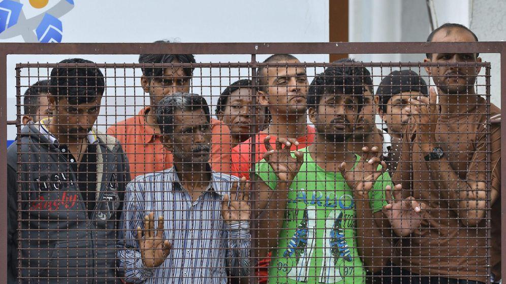 Foto: Varios inmigrantes observan a los policías que vigilan la entrada al campo de refugiados de Debrecen, en el este de Hungría. (Efe)