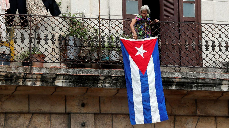 Foto: Una mujer sale al balcón donde se expone una bandera cubana, en La Habana, Cuba. (EFE)