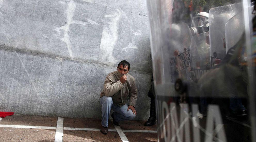 Foto: Un manifestante en una protesta contra las medidas de austeridad se protege del gas lacrimógeno en Atenas. (Reuters)