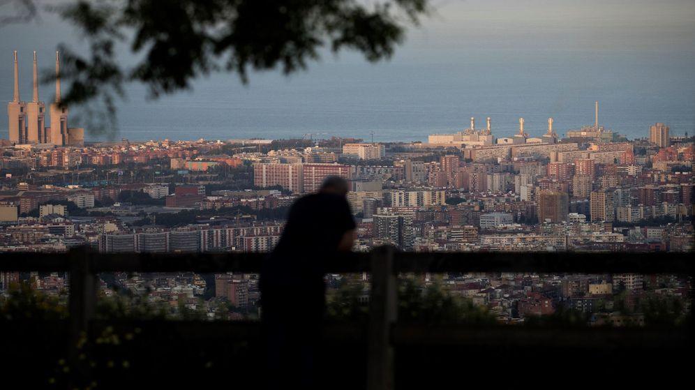 Foto: Un hombre observa la puesta de sol desde un mirador de la carretera del Tibiado en Barcelona. (EFE)