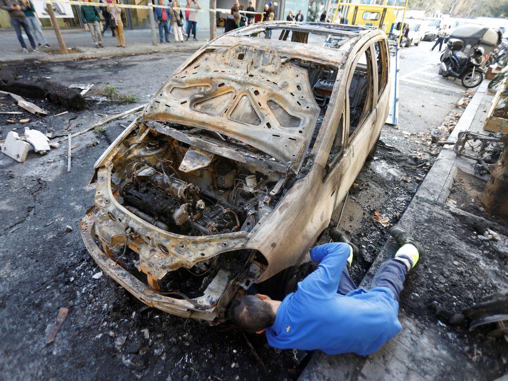 Foto: Un operario, junto a un coche quemado durante los disturbios del miércoles en Barcelona. (Reuters)