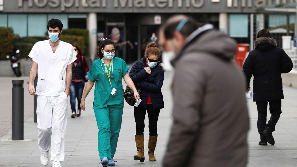 Foto: Trabajadores de la sanidad con mascarillas caminan junto a la entrada del hospital La Paz de Madrid. (EFE)