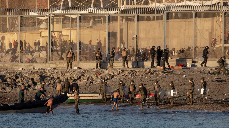 Miembros del Ejército ayudan a dos inmigrantes a su llegada a la playa de El Tarajal, junto a la valla fronteriza, en Ceuta. (EFE)