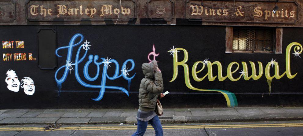 Foto: Una mujer pasa ante una pintada en Dublín que reza: Esta ciudad necesita esperanza y renovación (Reuters).