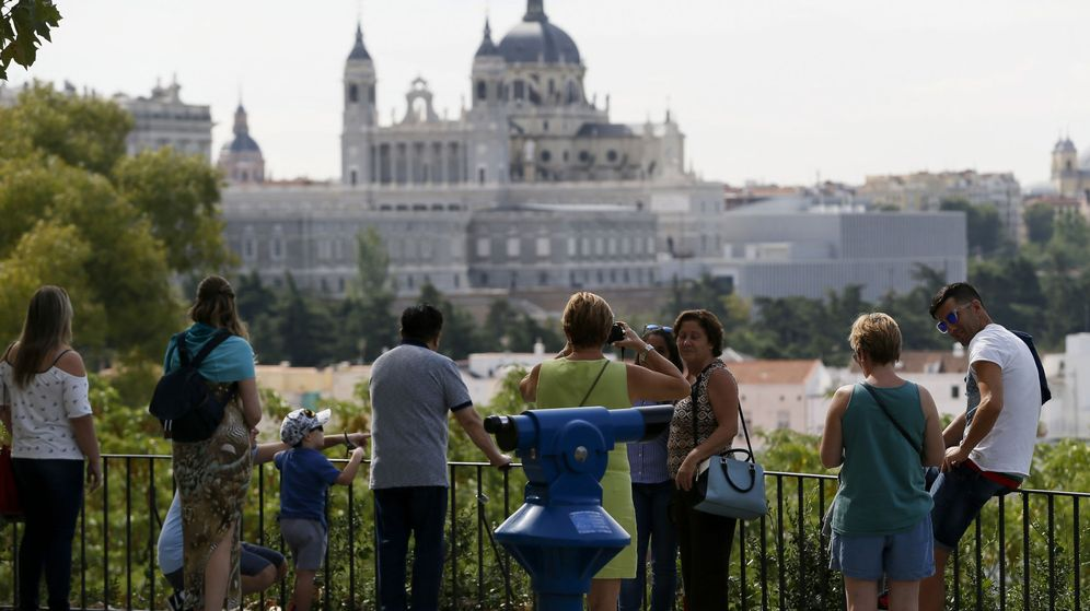 Foto: Varias personas observan las vistas del Palacio Real y la catedral de la Almudena desde los jardines del templo de Debod, en Madrid. (EFE)