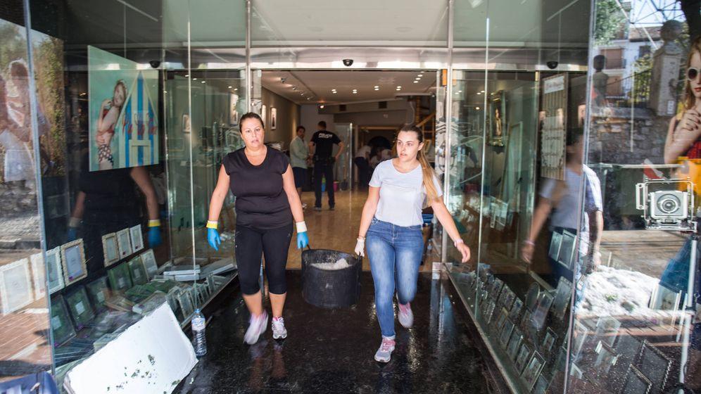 Foto: Dos empleadas de una tienda de fotografía retiran granizo del interior. (D. B.)