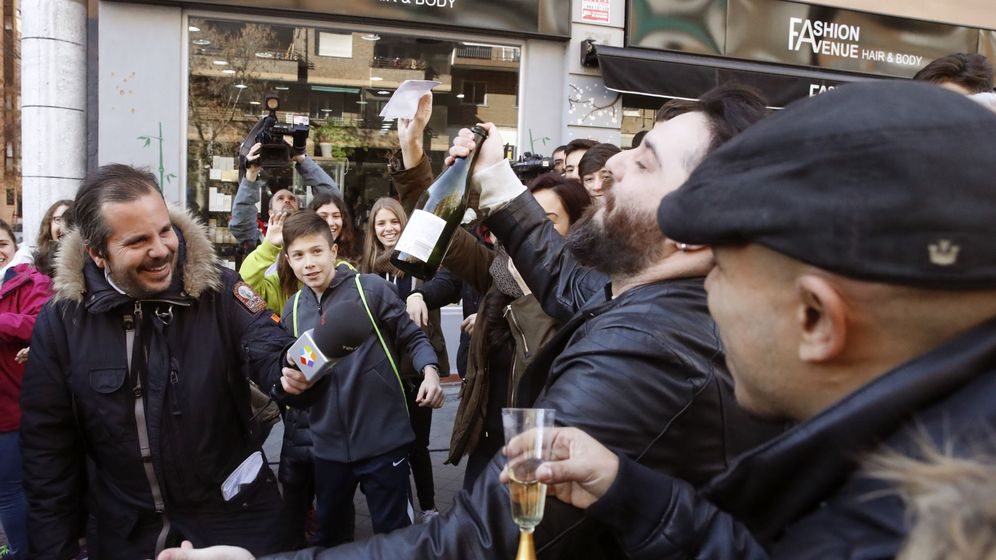 Foto: Varios vecinos brindan a las puertas de la administración situada en el Paseo de la Esperanza, número 4, en Madrid. (EFE)