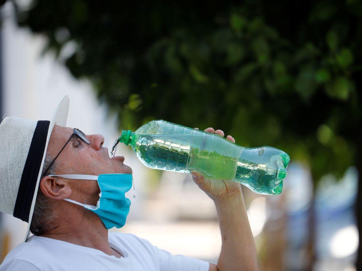 Foto: Un ciudadano se retira la mascarilla para beber. (EFE)