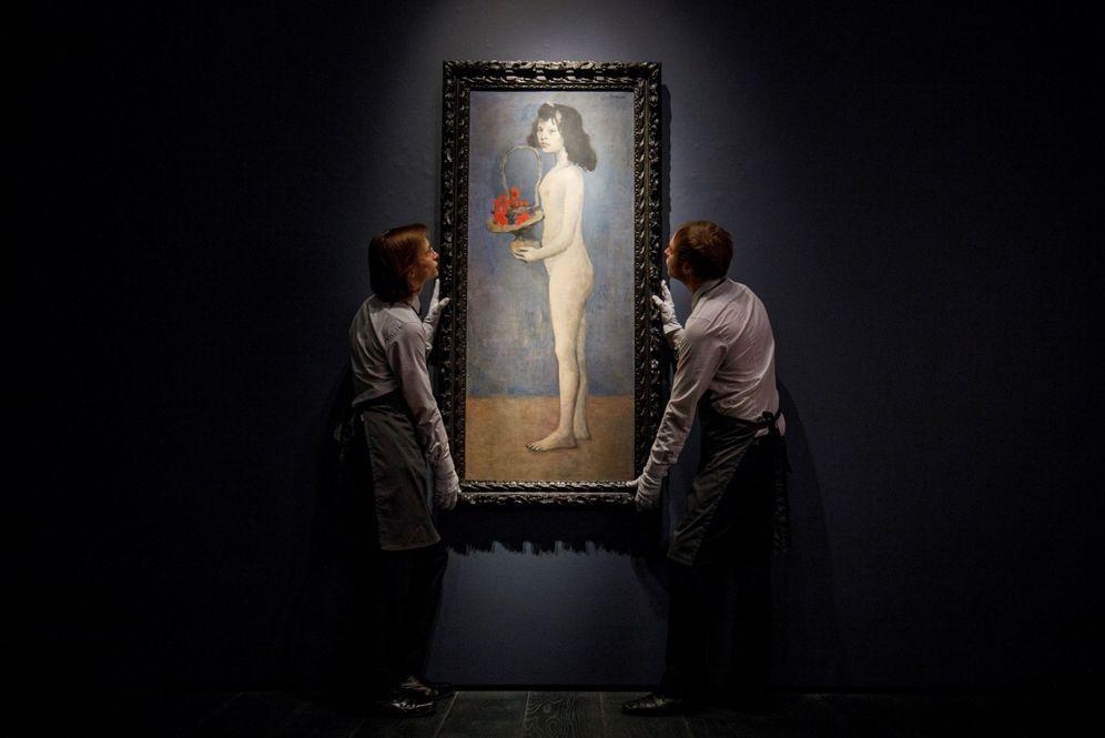 Foto: Trabajadores de la casa de subastas Christie's colocan la obra 'Joven con una cesta de flores', del artista español Pablo Picasso, que ha sido vendida por más de 100 millones. (EFE)