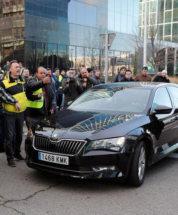 Foto: Un grupo de taxistas ante un vehículo con licencia VTC. (EFE)