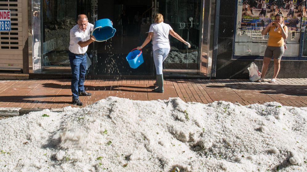 Foto: Comerciantes de Arganda del Rey sacan cubos de granizo de una tienda. (D.B.)