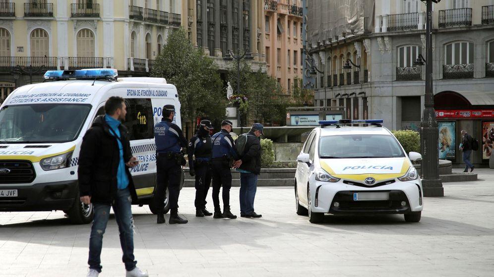 Foto: Miembros de la Policía Municipal esposan a un viandante tras avisarle de las limitaciones. (EFE)