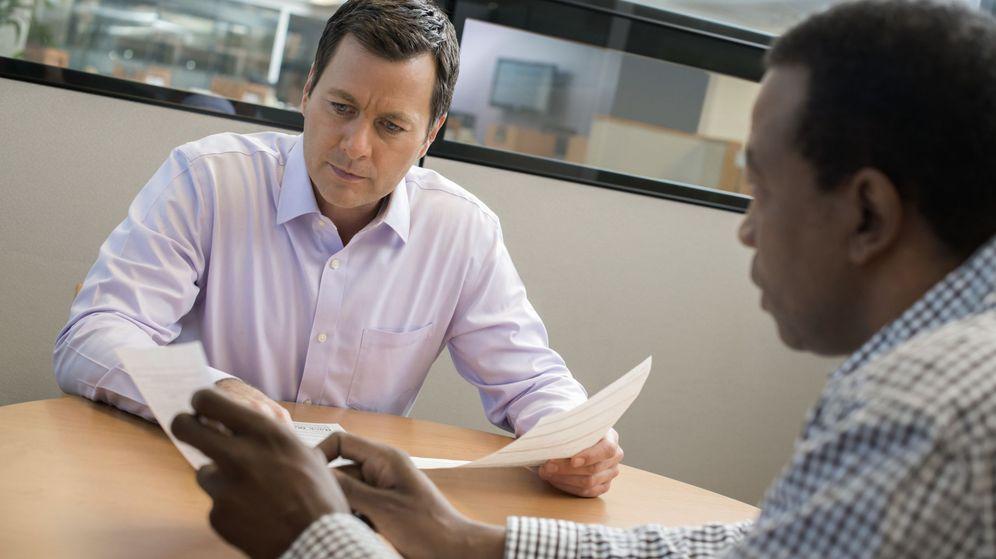 Foto: Un empleado de banca explicando los términos de un contrato a un cliente. (Corbis)