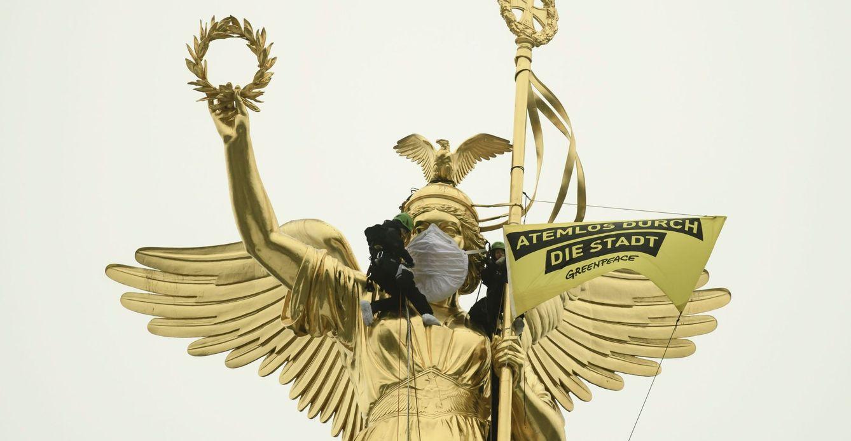 Activistas de Greenpeace colocan una marcarilla de portección en el rostro de la escultura de la Victoria en Berlín. (EFE)