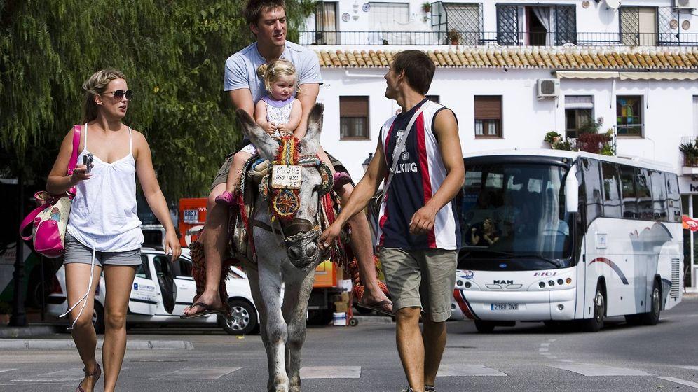 Foto: Unos turistas pasean en un burro-taxi en Mijas. (EFE)