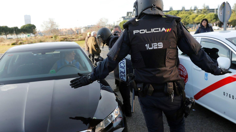 Un policía entre un VTC y un taxi. (EFE)