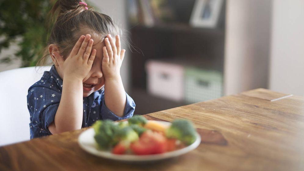 Foto: Una niña se echa las manos a la cabeza frente a un plato de verduras. (iStock)