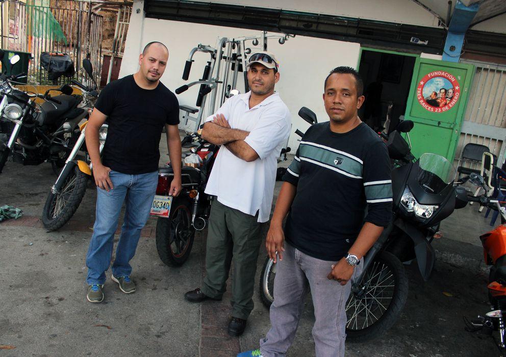 Foto: Miembros del colectivo Tres Raíces posan ante la puerta de su sede, en el barrio 23 de enero en Caracas, Venezuela (Andros Lozano).