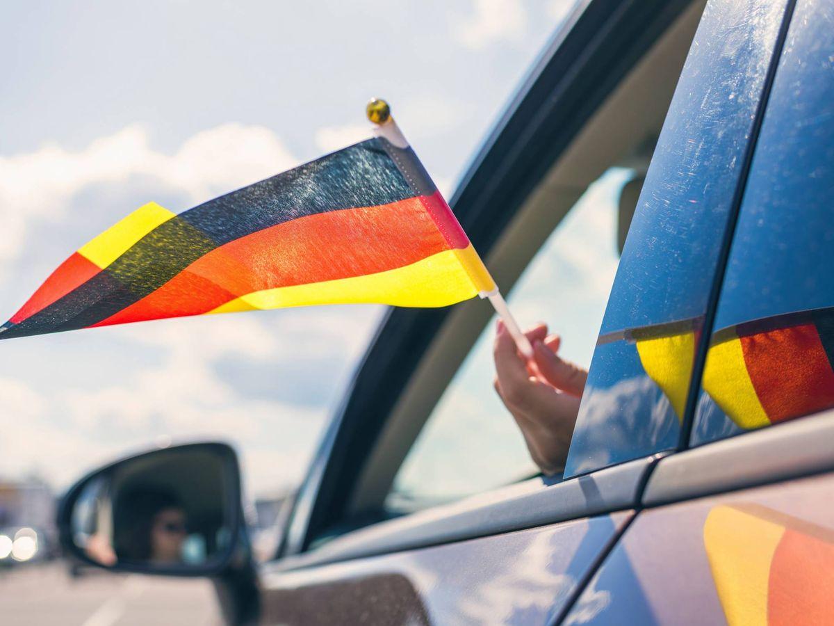 Foto: Mujer sujetando una bandera de Alemania mientras conduce. (iStock)