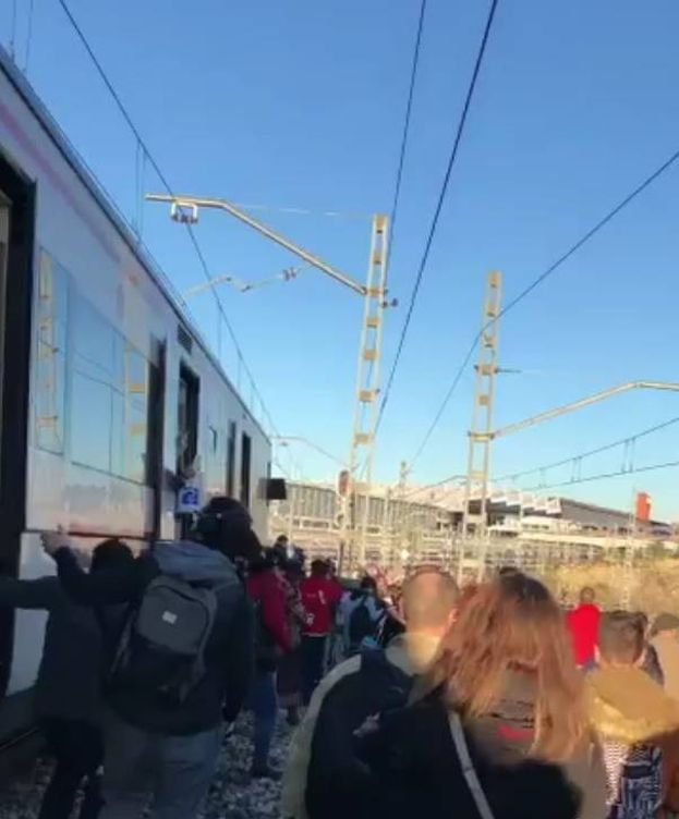 Foto: Varios viajeros caminan por las vías de Atocha. (@_OscarCollado)