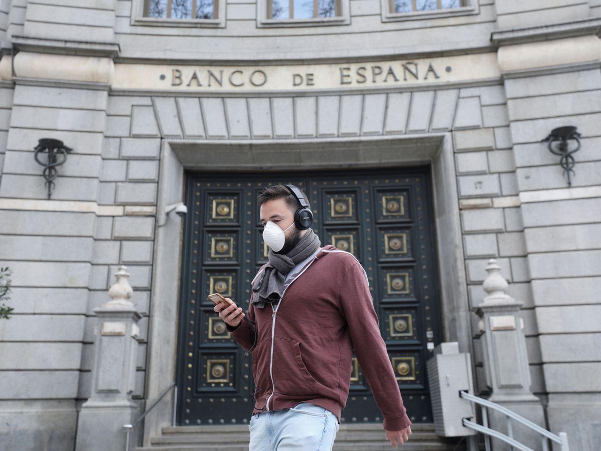 Foto: Una persona lleva una mascarillas de protección delante del Banco de España. (EFE)
