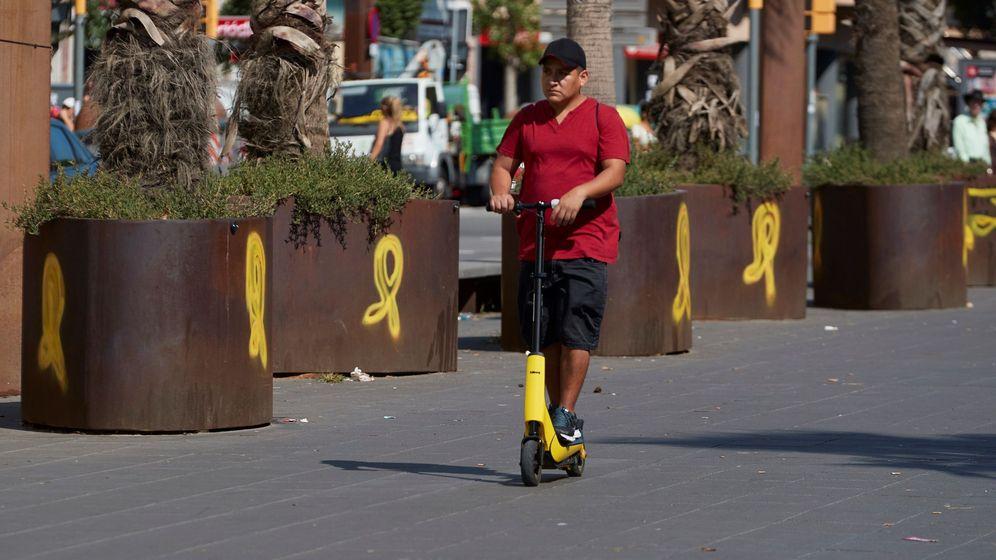 Foto: Un joven circula con su patinete ante unos lazos amarillos en el barrio de Sants de Barcelona. (EFE)