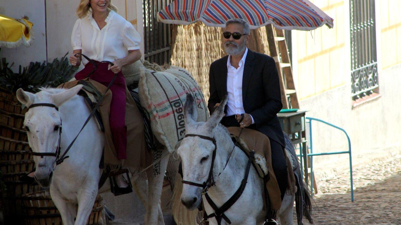 George Clooney, a lomos de un burro, junto a la actriz Brie Larson. (EFE)