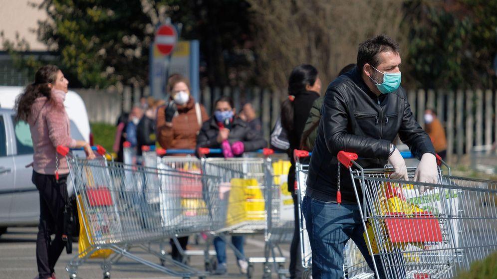 Foto: Varios ciudadanos hacen fila para hacer la compra en la ciudad itaiana de Desio. (EFE)