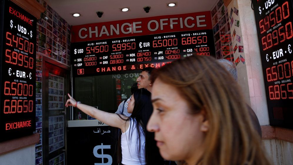 Foto: People check currency exchange rates at a currency exchange office in istanbul