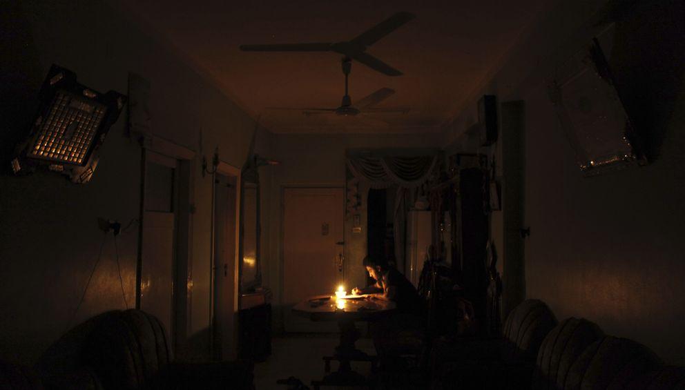 Un joven estudia durante la noche en medio de un corte de electricidad en Toukh (Reuters).