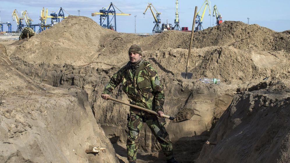 Foto: Un soldado ucraniano cava trincheras en una playa en el puerto de Mariúpol, en el mar de Azov. (Reuters)