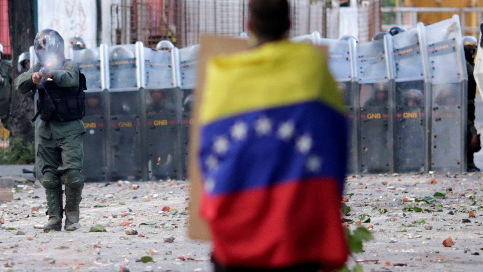 Foto: Un opositor frente a efectivos de las fuerzas de seguridad venezolanas durante una protesta opositoras en Caracas. (Reuters)