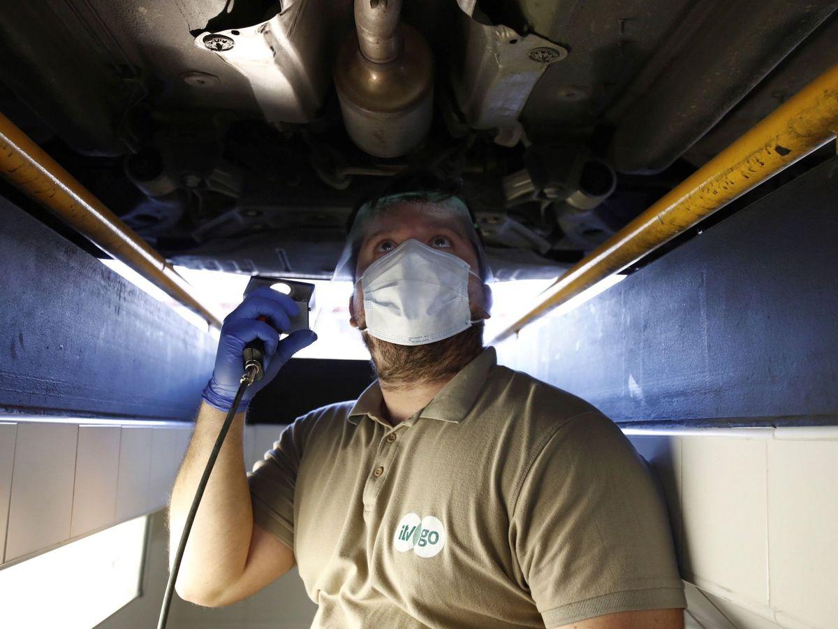 Foto: Un operario de la ITV pasa revisión a un coche. (EFE)