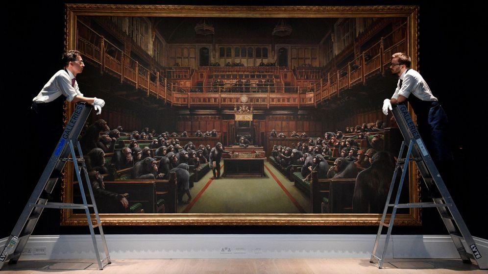Foto: Dos trabajadores posan junto a la obra 'Parlamento devuelto' del artista británico Banksy. (EFE)