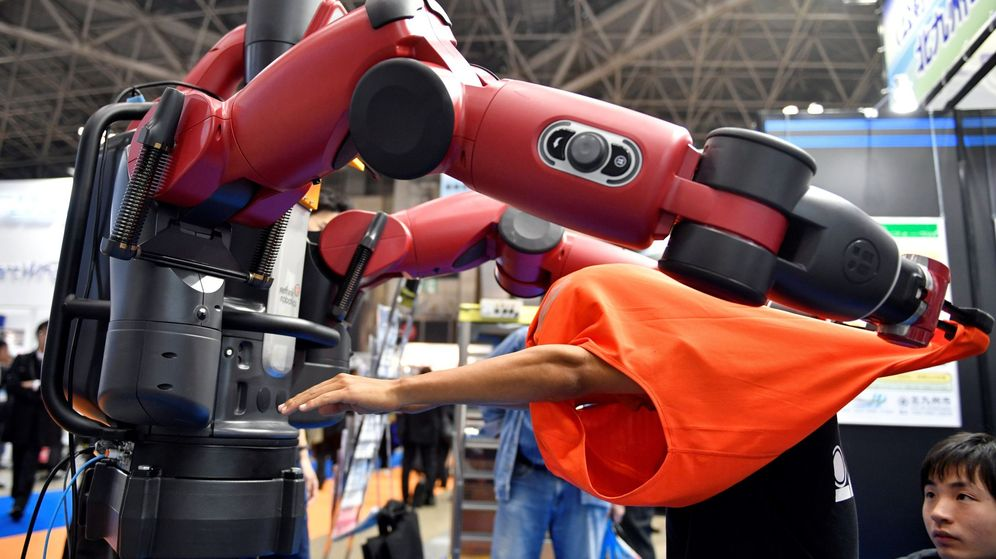 Foto: Un robot de asistencia del Instituto de Tecnología Kyushu ayuda a vestirse a un voluntario durante una demostración. (EFE)