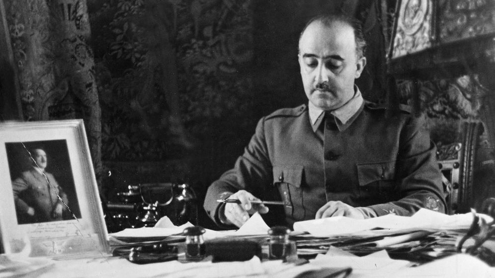 Foto: Franco, firmando documentos ante la atenta mirada de un retrato de Hitler. (Cordon Press)